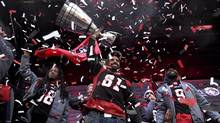 Ottawa Redblacks' Patrick Lavoie raises the Grey Cup over his head during a rally at Aberdeen Square, celebrating the team's victory over the Calgary Stampeders, Tuesday, Nov. 29, 2016 in Ottawa. (Justin Tang/THE CANADIAN PRESS)
