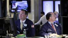 Specialists Charles Boeddinghaus, left, and Douglas Johnson, work at their posts on the floor of the New York Stock Exchange Tuesday, July 17, 2012. (Richard Drew/AP)