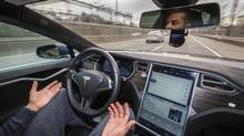 Ahmed Karam takes his hands off the steering wheel as his Tesla Model S drives in autopilot mode in Toronto on Feb. 20. (Mark Blinch/Globe and Mail)