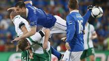 Italy's Thiago Motta, top, jumps over Ireland's Glenn Whelan and Jon Walters during the Euro 2012 soccer championship Group C match between Italy and the Republic of Ireland in Poznan, Poland, Monday, June 18, 2012. (Peter Morrison/Associated Press)