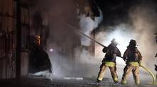 Firefighters work to bring a blaze under control at the Classy Lane Stables, in Puslinch, Ont., on January 5, 2015. Forty horses were killed when a fire engulfed a stable building at the facility near Guelph, Ontario.