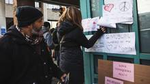 A woman adds a note to the supportive signs posted outside the Masjid Toronto mosque on Feb. 17, 2017. (JENNIFER ROBERTS/JENNIFER ROBERTS FOR)
