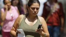 A woman uses her mobile device while walking in downtown Chicago on July, 29, 2008. (M. Spencer Green)