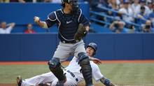 Toronto Blue Jays third baseman Brett Lawrie (13) is forced out at home plate in the second inning as Minnesota Twins catcher Kurt Suzuki (8) makes the putout at Rogers Centre on June 10, 2014. (Tom Szczerbowski/USA Today Sports)