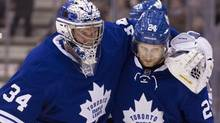 In this file photo, Toronto Maple Leafs goaltender James Reimer (left) is helped off the ice by John-Michael Liles during second period NHL hockey action against Philadelphia Flyers in Toronto on Monday February 11, 2013. After the signing of Cody Franson on Thursday, Liles could find himself on waivers ahead of the NHL's Monday roster deadline writes Globe and Mail hockey reporter David Shoalts. (CHRIS YOUNG/THE CANADIAN PRESS)