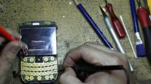 A man fixes a Blackberry phone for his client in his store in Jakarta in this April 17, 2012 file photo. (SUPRI/REUTERS)
