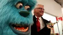 British Columbia past Premier Gordon Campbell stands next to a figure of Sulley, from the Pixar movie Monsters Inc., during the opening of Pixar Canada in Vancouver, B.C., on Tuesday April 20, 2010. (DARRYL DYCK FOR THE GLOBE AND MAIL)