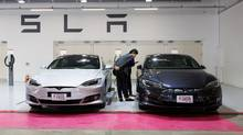 Customers look at Tesla Model S 90D electric vehicles parked at a charging station in a shopping complex in South Korea. (SeongJoon Cho/Bloomberg)