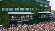 Crowds greet Britain's Andy Murray as he celebrates with the trophy on the balcony of Centre Court after winning the Men's singles title of the Wimbledon Championships at The All England Lawn Tennis and Croquet Club, Wimbledon, London, Sunday July 7, 2013. (Dominic Lipinski/AP)