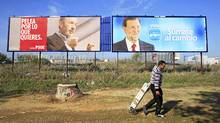 Juan Manuel Viedma, 27, an unemployed man who collects aluminium from garbage containers to sell it, walks past electoral posters of Prime ministerial candidate Alfredo Perez Rubalcaba (L) of the Spanish Socialist Workers' Party (Partido Socialista Obrero Espanol) and Spain's centre-right People's Party (Partido Popular) leader Mariano Rajoy in the Andalusian capital of Seville November 15, 2011. (Marcelo del Pozo/Marcelo del Pozo/REUTERS)