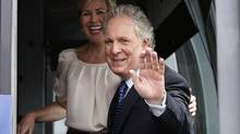 Quebec's Premier Jean Charest and his wife Michele Dionne (L) wave to people as he leaves the airport in his campaign bus in Quebec City, August, 1, 2012. (MATHIEU BELANGER/REUTERS)