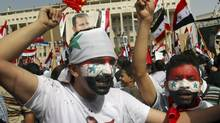 Syrian regime supporters paint the national flags on their faces as they shout slogans during a demonstration to show their support for President Bashar Assad in Damascus, Syria, on Wednesday Oct. 12, 2011. (Bassem Tellawi/AP)