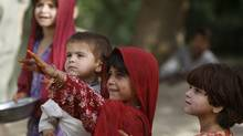An Afghan girl holding a baby asks for a pen from a Canadian army soldier from 5th platoon, bulldog company 1st Battalion, 22nd Royal Regiment as they patrol in the Panjwai district of Kandahar province southern Afghanistan, June 15, 2011. (Baz Ratner/Reuters/Baz Ratner/Reuters)