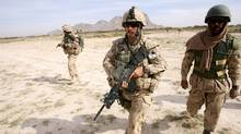 """Canadian soldiers from the Royal 22nd Regiment, who work with the Afghan National Army as an """"Observer Mentor Liasion Training"""" team, conduct a foot patrol in Panjwai district, Kandahar province in 2006. The man in the green helmet is a translator. (JOHN D MCHUGH)"""