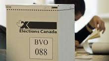 An Elections Canada worker checks a voter list at a Montreal polling station on May 2, 2011. (Graham Hughes/Graham Hughes/The Canadian Press)