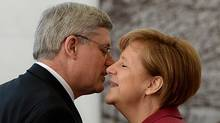 Prime Minister Stephen Harper is welcomed by German Chancellor Angela Merkel as he arrives to the Chancellery in Berlin, Germany on Thursday, March 27, 2014. (Sean Kilpatrick/THE CANADIAN PRESS)