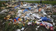 Flowers and mementos lie at the crash site of Flight MH17 near the settlement of Rozspyne in the Donetsk region of Ukraine. (MAXIM ZMEYEV/REUTERS)