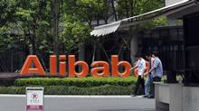 Young men walk past the corporate logo at the headquarters compound of Alibaba Group in Hangzhou in eastern China's Zhejiang province in this May 21, 2012 file photo. (AP)