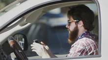FILE - In this Feb. 26, 2013 file photo, a man uses his cell phone as he drives through traffic in Dallas. (LM Otero/AP PHOTO)