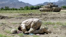 An Afghan military interpreter prays just before the storming of Salavat, Afghanistan, on Thursday, June 18, 2009. (Colin Perkel/THE CANADIAN PRESS)