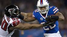 Buffalo Bills running back running back Fred Jackson holds off Atlanta Falcons defensive end Osi Umenyiora (50) during first half NFL action in Toronto on Sunday December 1, 2013. (FRANK GUNN/THE CANADIAN PRESS)