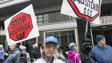A man holds up signs during a demonstration outside Bombardier's head office in Montreal, Sunday, April 2, 2017, to protest recent pay hikes and bonuses to the company's top executives. (Graham Hughes/THE CANADIAN PRESS)