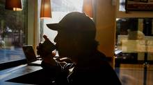 The silhouette of a customer drinking a cup of coffee is seen at a Tim Hortons Inc. restaurant in downtown Vancouver, British Columbia, Canada, on Tuesday, Aug. 26, 2014.