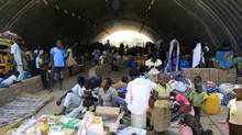 Families displaced by recent fighting in South Sudan, camp in a warehouse inside the United Nations Mission in Sudan (UNAMIS) facility in Jabel, on the outskirts of capital Juba December 23, 2013. Clashes between rival groups of soldiers in Juba a week ago have spread across the country, which won its independence from Sudan in 2011 after decades of war. President Salva Kiir, from South Sudan's Dinka ethnic group, has accused former Vice President Riek Machar, a Nuer whom he dismissed in July, of trying to launch a coup. Machar dismissed the charge but has since said he is commanding troops fighting the government. (JAMES AKENA/REUTERS)