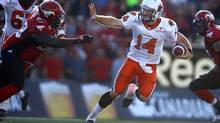 B.C.Lions' quarterback Travis Lulay, right, gets chased by Calgary Stampeders' Torrey Davis during first half CFL action in Calgary, Alta., Saturday, July 28, 2012. (Jeff McIntosh/THE CANADIAN PRESS)