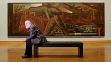 Charlie Hill, the National Gallery of Canada's curator of Canadian art, is photographed in Ottawa in front of Charles F. Comfort's painting The Romance of Nickel, 1937. (Dave Chan for The Globe and Mail)