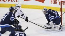 Winnipeg Jets goaltender Ondrej Pavelec (31) saves the shot from Los Angeles Kings' Tyler Toffoli (73) as Jets' Julian Melchiori (71) and Chris Thorburn (22) defend during first period NHL action in Winnipeg on Thursday, March 24, 2016. (JOHN WOODS/THE CANADIAN PRESS)