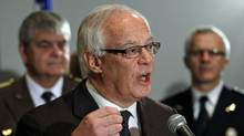 Flanked by police, Public Security Minister Robert Dutil announces Quebec's decision to take the federal government to court over its plan to destroy gun-registry data at a Quebec City news conference on Dec. 13, 2011. (Jacques Boissinot/Jacques Boissinot/The Canadian Press)