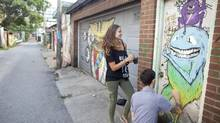 Artists Alice Blastorah, left, and Justin Pape, right, work on a mural behind Ossington Avenue Sunday, August 12, 2012 in Toronto. (Brett Gundlock/Brett Gundlock for the Globe and Mail)