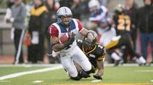 Montreal Alouettes strong back Arland Bruce is tackled during a CFL game in 2013. After his final season, Bruce soon became the face of concussions and football in Canada. (Frank Gunn/The Canadian Press)