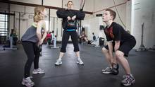 Two youngsters share a workout with trainning coach Laura MacDonald at CrossFit Gym in Calgary in early 2010 (Chris Bolin/© 2010 Chris Bolin Photography Inc.)