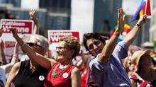Ontario Premier Kathleen Wynne, left, who is Canada's first openly-gay premier, walks with Liberal Party Leader Justin Trudeau, right, during the 33rd annual Pride Parade in Toronto on Sunday, June 30, 2013 (Michelle Siu/THE CANADIAN PRESS)