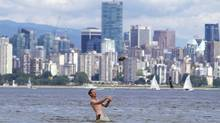 A man leaps for a football with the Vancouver skyline in the background while playing at Spanish Banks on June 8, 2014. (Ben Nelms for The Globe and Mail)