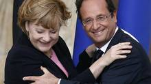 German Chancellor Angela Merkel and French President Francois Hollande smile after kissing each other in Reims July 8, 2012, during the 50th anniversary ceremony of the reconciliation meeting between Charles de Gaulle and Konrad Adenauer after the Second World War. (JACKY NAEGELEN/REUTERS)