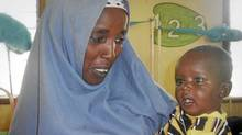 In this photo released by the International Rescue Committee, Minhaj Gedi Farah is held in the arms of his mother Asiah Dagane in the International Rescue Committee (IRC) hospital in Dadaab, Kenya Wednesday, Oct. 19, 2011. (Edward Macharia/Edward Macharia/AP)