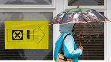 A woman carries an umbrella as she enters a polling station to vote in the federal election in Sidney, B.C., on Vancouver Island, on Monday May 2, 2011. (Darryl Dyck/ The Globe and Mail/Darryl Dyck/ The Globe and Mail)