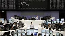 Traders work at their desks in front of the DAX board at the Frankfurt stock exchange on May 22, 2012. (KIRILL IORDANSKY/REUTERS)