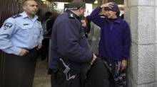 Bonna Devora Haberman, of Women of the Wall, is confronted by police after trying to bring in her prayer shawl at entrance of the Western Wall in Jerusalem, Dec. 14, 2012. (RINA CASTELNUOVO/NYT)