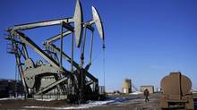 A man walks past a Lufkin oil drilling pump in McKenzie County outside of Williston, North Dakota in this file photo taken March 12, 2013. (Shannon Stapleton/Reuters)