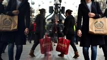 The next three months, with Halloween and the Christmas shopping season, are the toughest time of the year for personal finance, columnist Rob Carrick says. Shoppers are reflected in a shop window as they walk along Oxford Street, one of the main shopping streets in central London, on December 22, 2015. Britain's retail sales rebounded sharply in November, helped by buying on 'Black Friday' when items are heavily discounted in the run-up to Christmas, official data showed last week. AFP PHOTO / BEN STANSALLBEN STANSALL/AFP/Getty Images (BEN STANSALL/AFP/Getty Images)