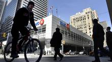 Pedestrians cross the street in front of The Bank of Montreal in downtown Toronto. (Fred Lum/The Globe and Mail)