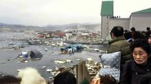 People look at the aftermath of tsunami tidal waves covering a port at Kesennuma in northern Japan. (Keichi Nakane/Keichi Nakane/The Yomiuri Shimbun/AP)