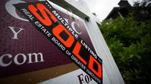 A sold sticker is seen placed on a for sale sign outside a house in east Vancouver, B.C., on Sunday September 20, 2015. (DARRYL DYCK For The Globe and Mail)