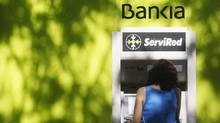 A woman withdraws money from an ATM machine at Spain's lender bank Bankia in Madrid (Reuters)