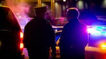 RCMP Inspector Bryon Massie, left, speaks with an investigator outside a banquet hall where four men were shot in Richmond, B.C., on Jan. 16, 2013. (Darryl Dyck/The Canadian Press)