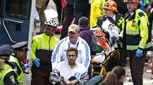 Medical workers aid injured people at the finish line of the 2013 Boston Marathon following two nearby explosions on Monday, April 15, 2013. (Charles Krupa/The Associated Press)